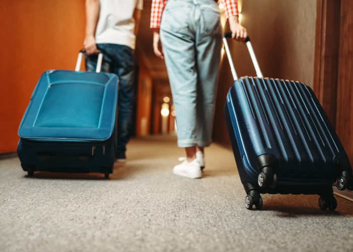 Two people wheeling rolling suitcases down a hotel hallway