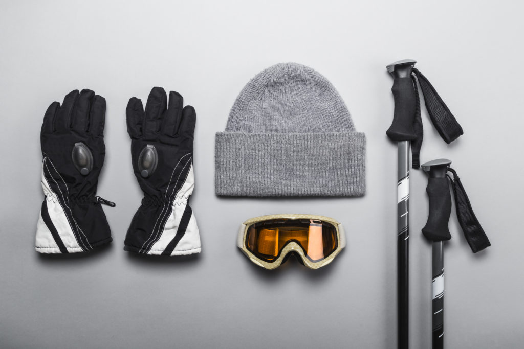 Winter sports gear laid out on a flat grey backdrop