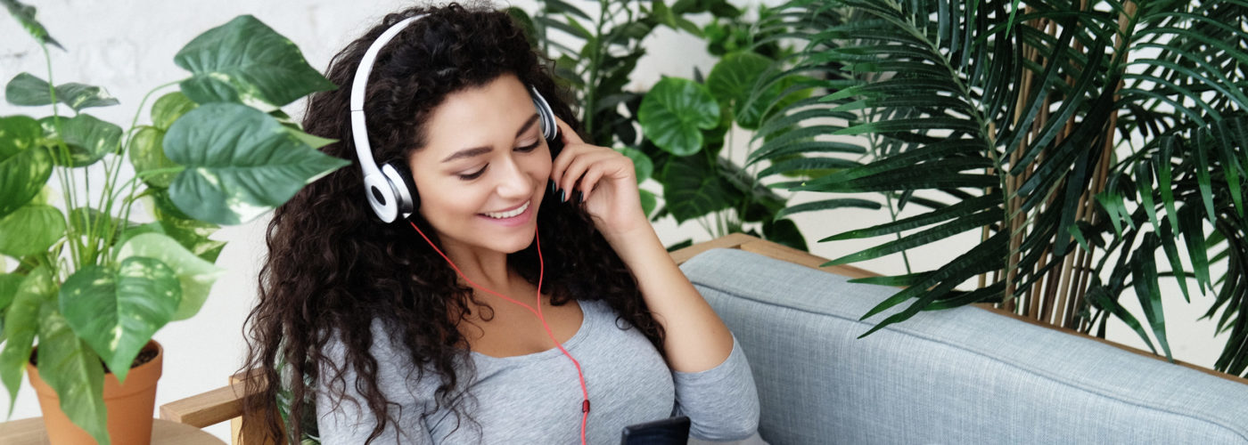 Women sitting amongst houseplants on a sofa listening to music on her phone