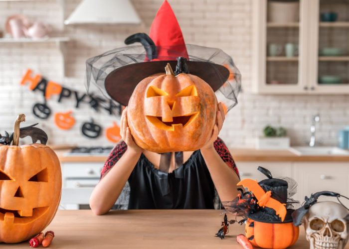 Woman dressed as a witch holding a jack-o-lantern in front of her face