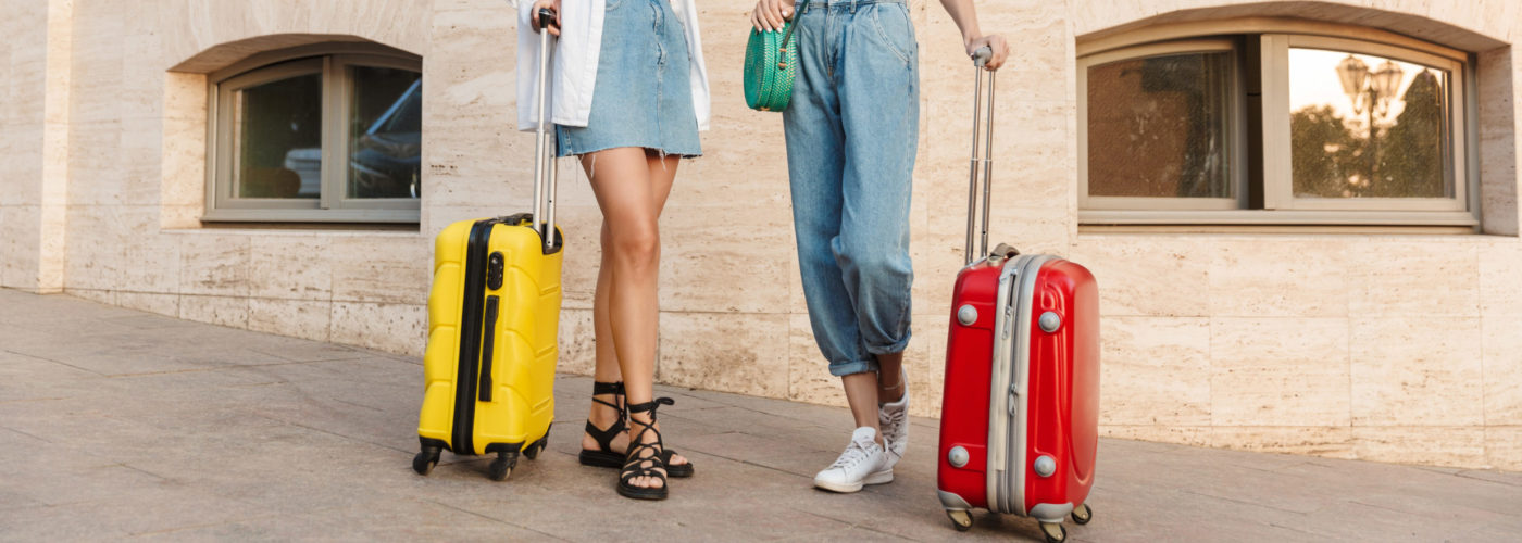 Two tourists on a street with two suitcases