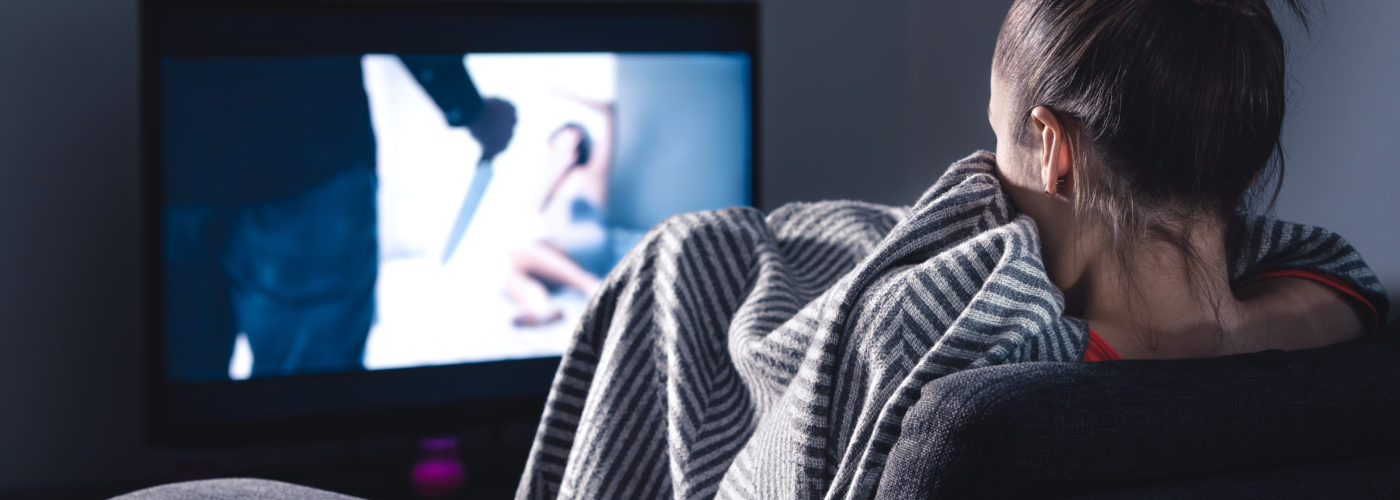 Woman watching scary movie on screen