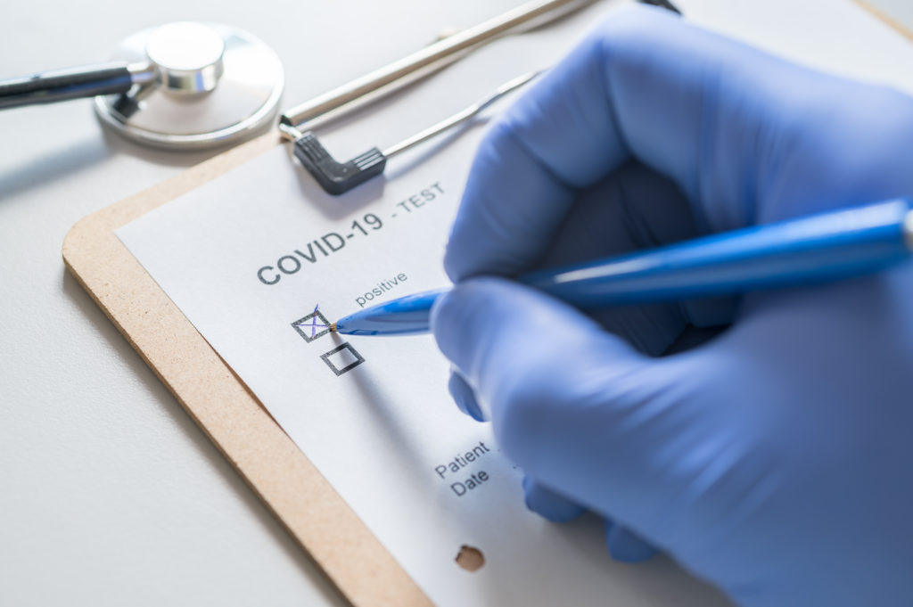 Person wearing gloves marking down a positive result from a COVID-19 test on a clip board