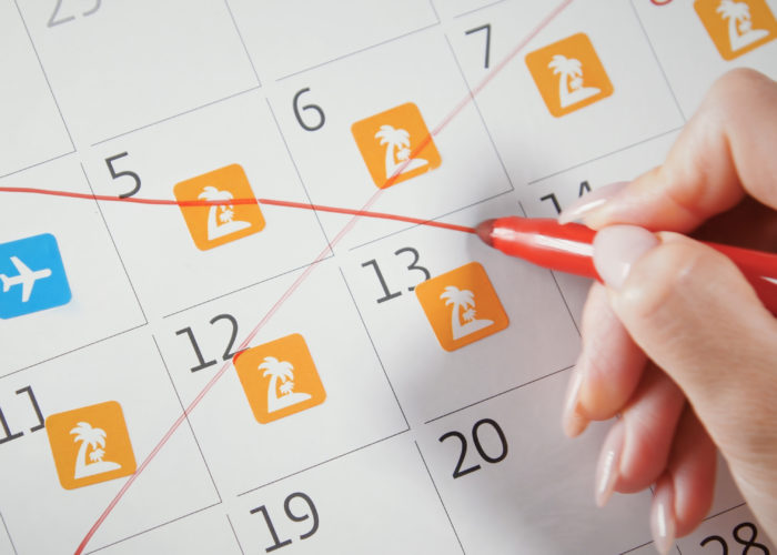 Person crossing out vacation plans on whiteboard calendar