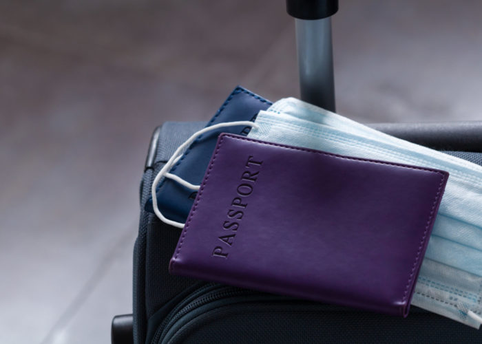 Purple suitcase with masks and passport on top