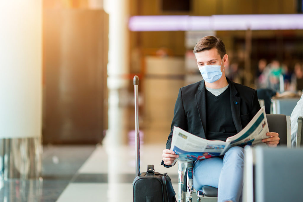 Man reading a newspaper, wearing a mask in an airport terminal