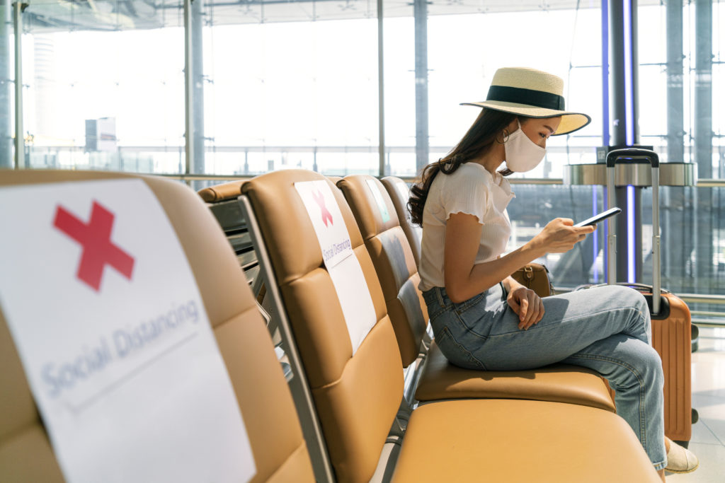 Woman wearing a mask, waiting in social distanced airport terminal