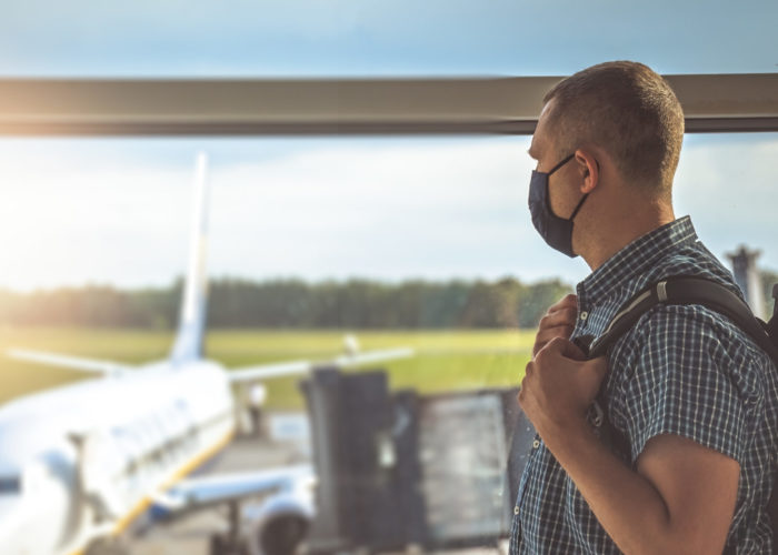 Man wearing a face mask and looking out an airport window at a plane on the tarmac
