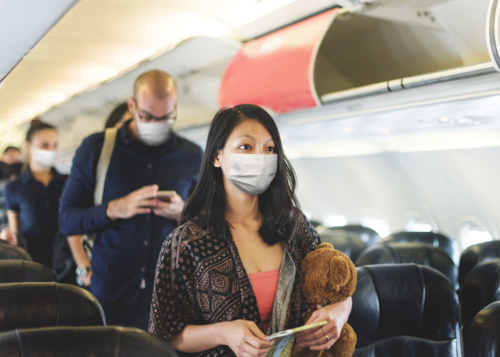 A line of people looking for their seats on the plane and wearing protective face masks