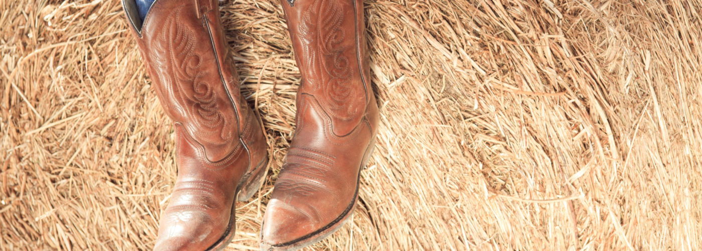 Person from the knees down wearing cowboy boots resting on a pile of hay