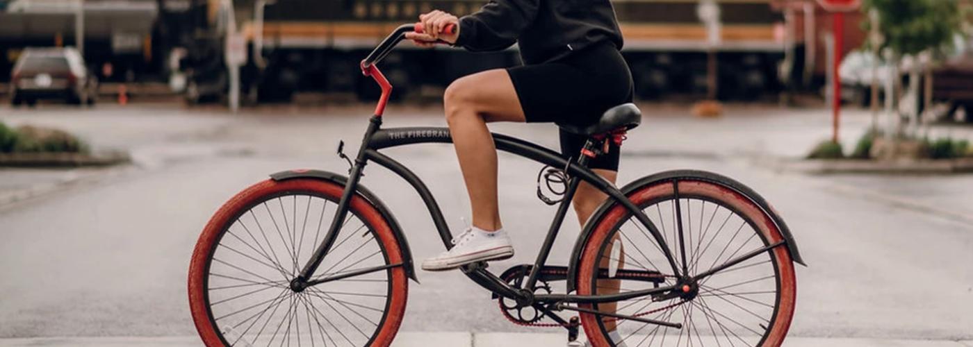 Woman riding a bike wearing Aspen Reprise biker shorts