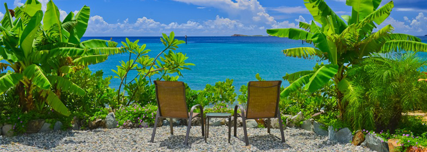 Two beach chairs overlooking the ocean and tropical greenery