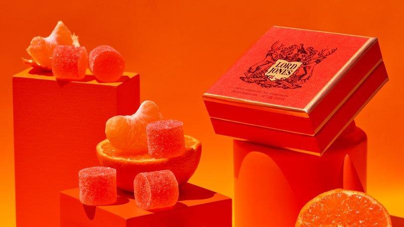 A box of Lord Jones CBD Gumdrops and a few loose drops on an orange backdrop