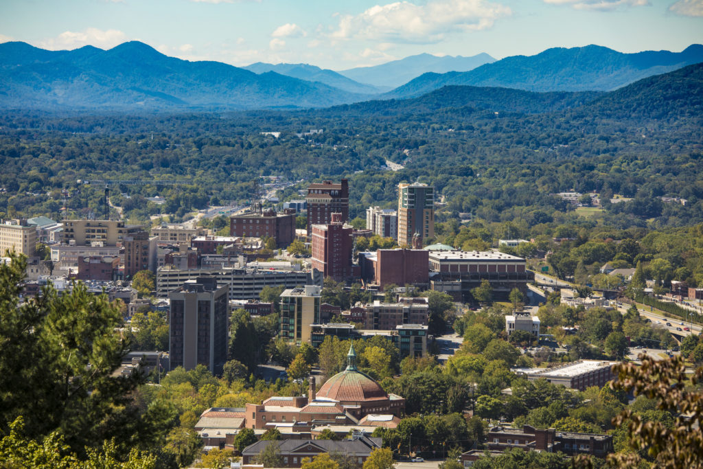 Aerial view of Asheville, North Carolina with a backdrop of the Blueridge Mountains