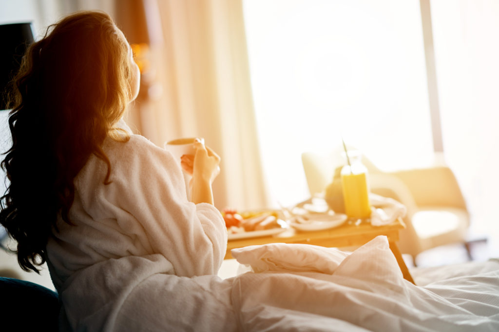 Woman looking out a bright window, having breakfast in bed at hotel