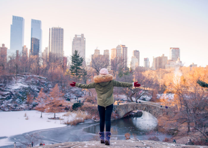 Woman gesturing with wide arms to a snow covered Central Park