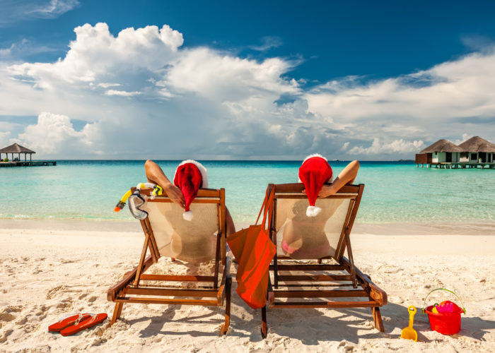 Couple sitting on lounge chairs on the beach in Santa hats