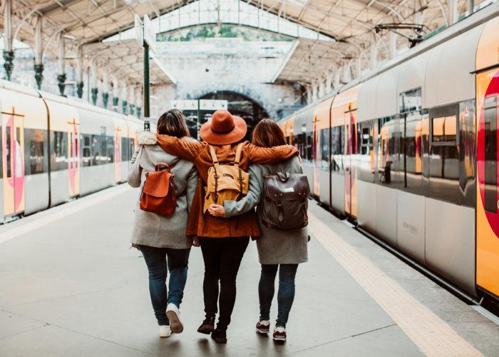 Three friends facing away from camera at train station