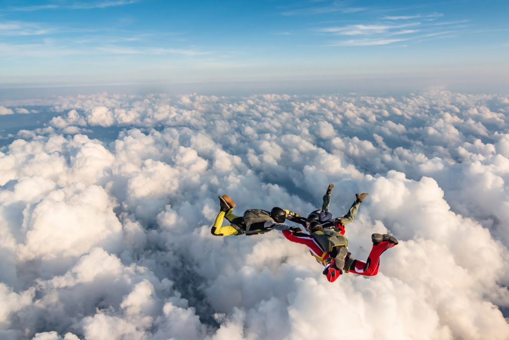Three people skydiving above the clouds