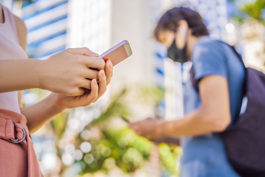 A woman, in focus in the foreground, using her smartphone and a man, out of focus in the background, also using his smartphone and wearing a face mask
