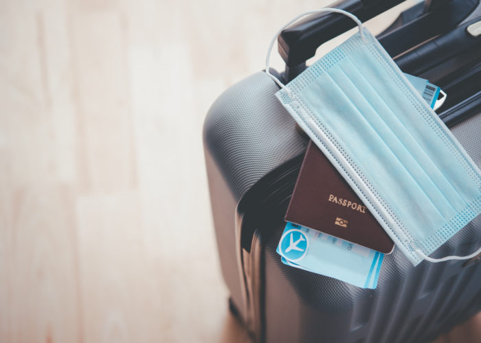 Luggage with passport, boarding passes, and face mask on top