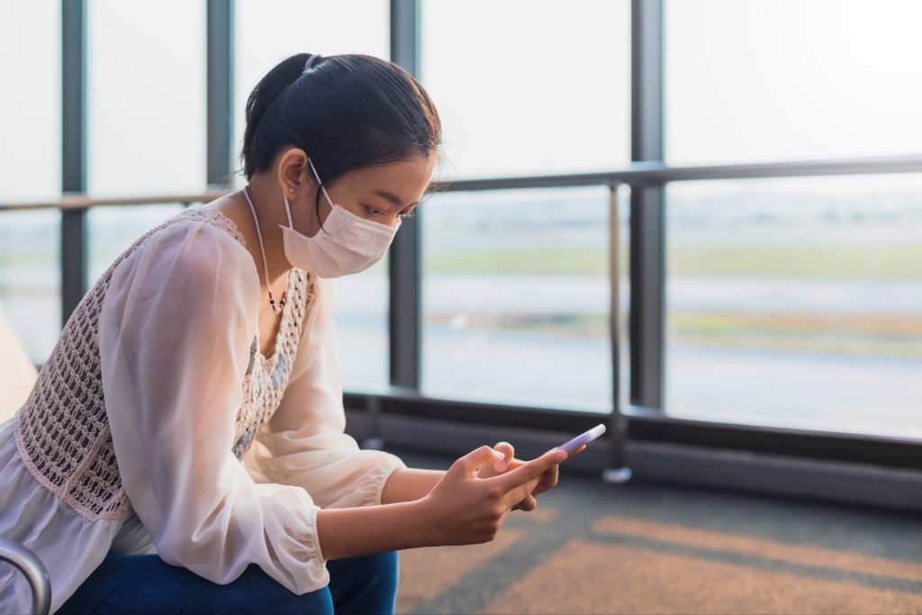 Woman sitting in airport terminal, wearing a face mask and using her smartphone