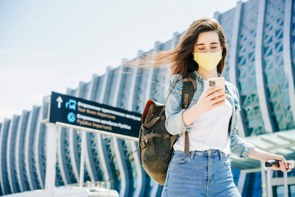 Woman walking away from an airport terminal, wearing a face mask and using her smartphone