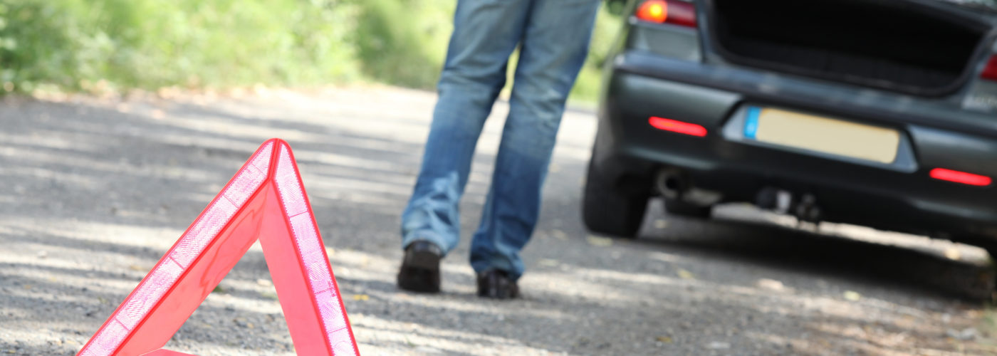 Man setting out hazard triangle from car emergency kit at breakdown