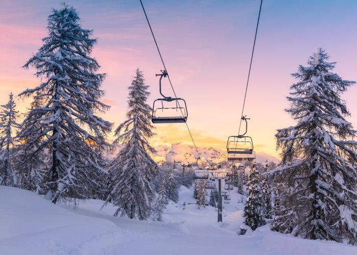Ski lift on a snowy mountain at sunrise